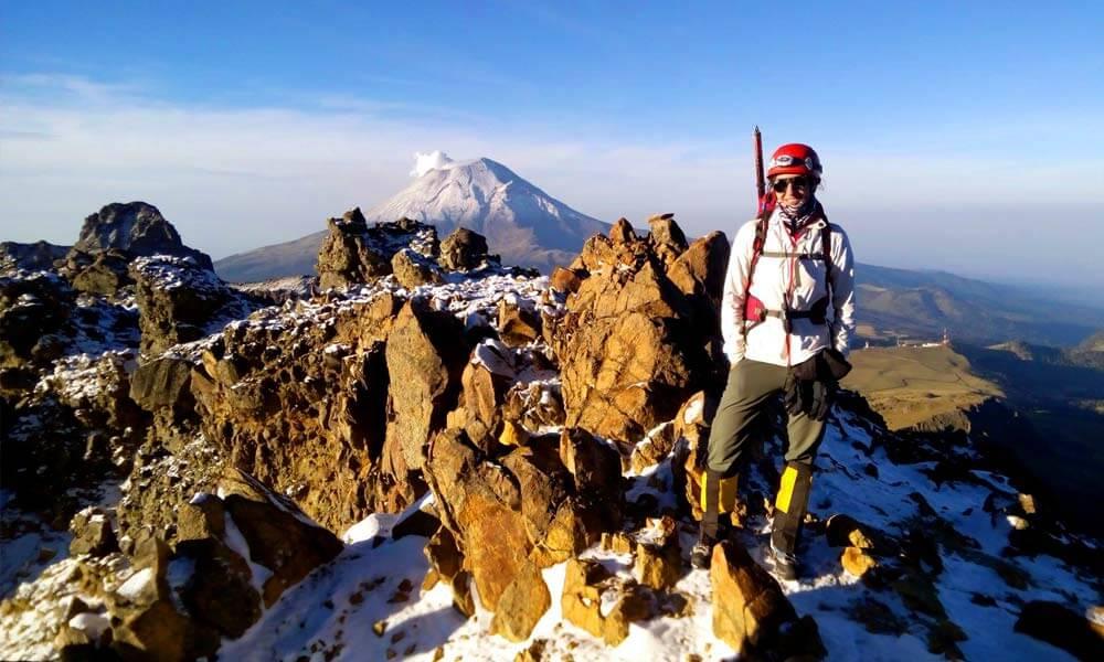 Mariana Torres en la cima del Iztaccihuatl, atrás el Popocatépetl